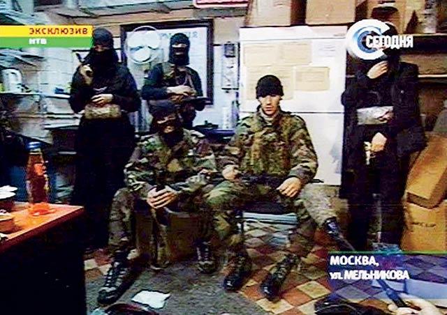 Мовсар Бараев (сидит справа) поначалу считался главарём террористов. Он единственный, кто во время захвата ДК на Дубровке не скрывал своего лица. Он же давал интервью телеканалу НТВ. Но на самом деле главарем был Руслан Эльмурзаев по кличке Абубакар (сидит слева).